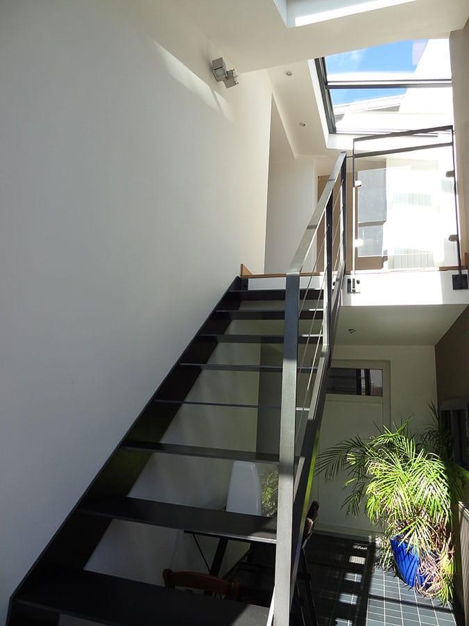 Extension dédiée à la création d'une entrée dans la maison avec un escalier en métal laqué