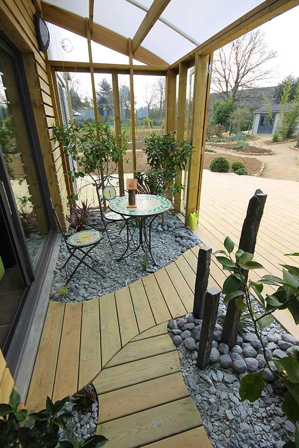 Dans le jardin d'hiver, un petit passage en terrasse bois dans le Morbihan