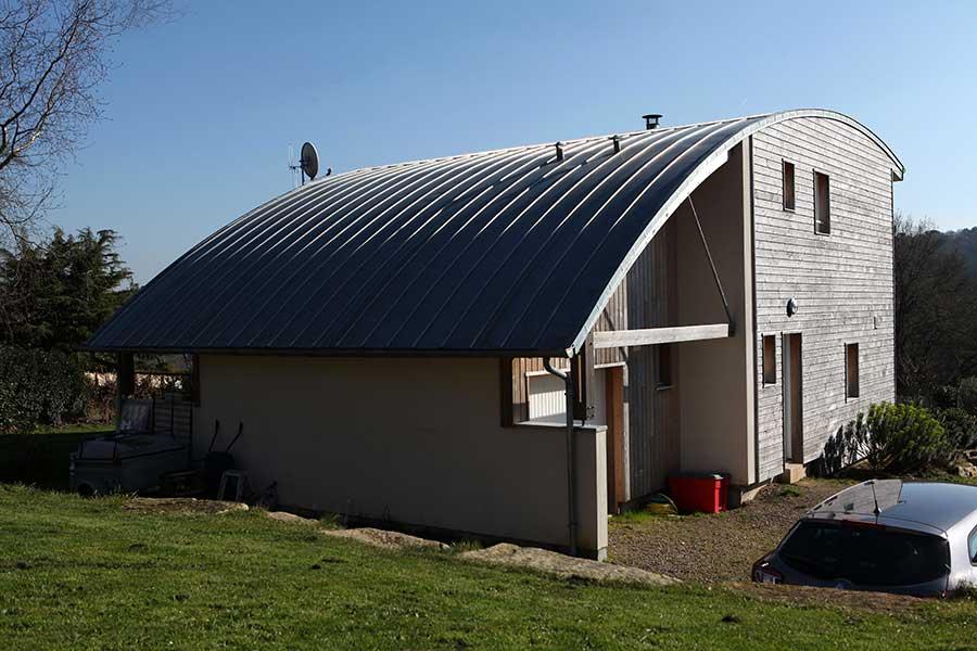 Construction d'une maison à ossature bois (bardage en douglas) avec toiture cintrée en zinc, proche de Meucon dans le Morbihan