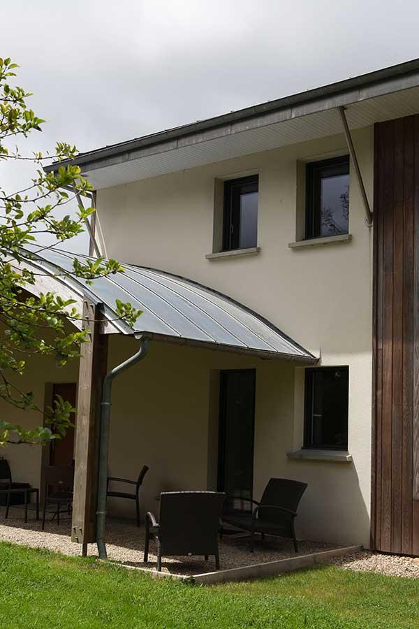 Construction d'une maison en bois et murs traditionnels, toiture courbe zinc, dans le Morbihan
