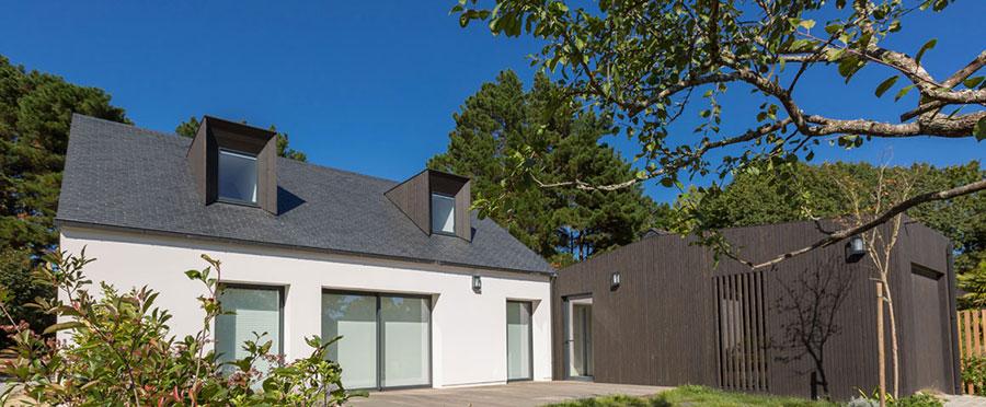 Adjonction d'un local garage/patio/cuisine (bardage bois à lames verticales traité en noir) sur une maison traditionnelle relookée suite à isolation par l'extérieur, dans le Morbihan