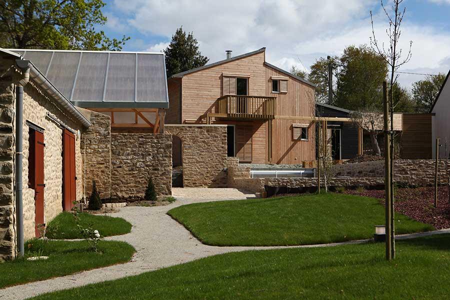 Construction d'une maison à ossature bois (bardage douglas) avec toitures monopentes en zinc, dans le Morbihan