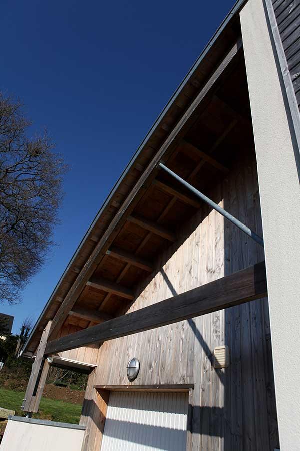 Construction d'une maison à ossature bois (bardage en douglas) avec toiture cintrée en zinc, dans le Morbihan