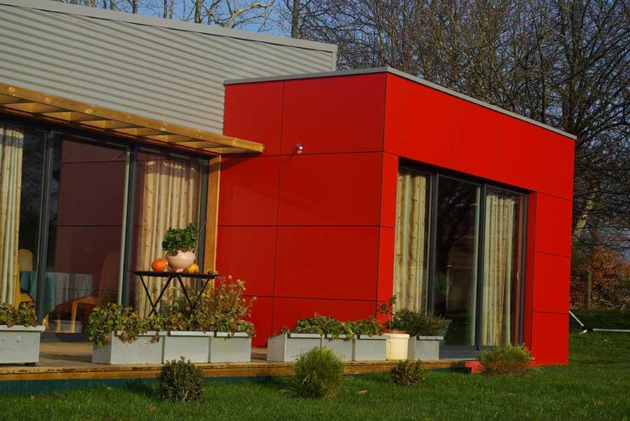 Detail de bardage composite rouge sur maison ossature bois dans le Morbihan