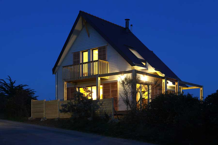 Construction d'une maison à ossature bois (bardage en bois peint) avec toitures en ardoise, dans le Morbihan